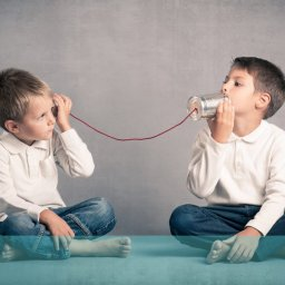 Picture of two children using a tin and string phone to speak