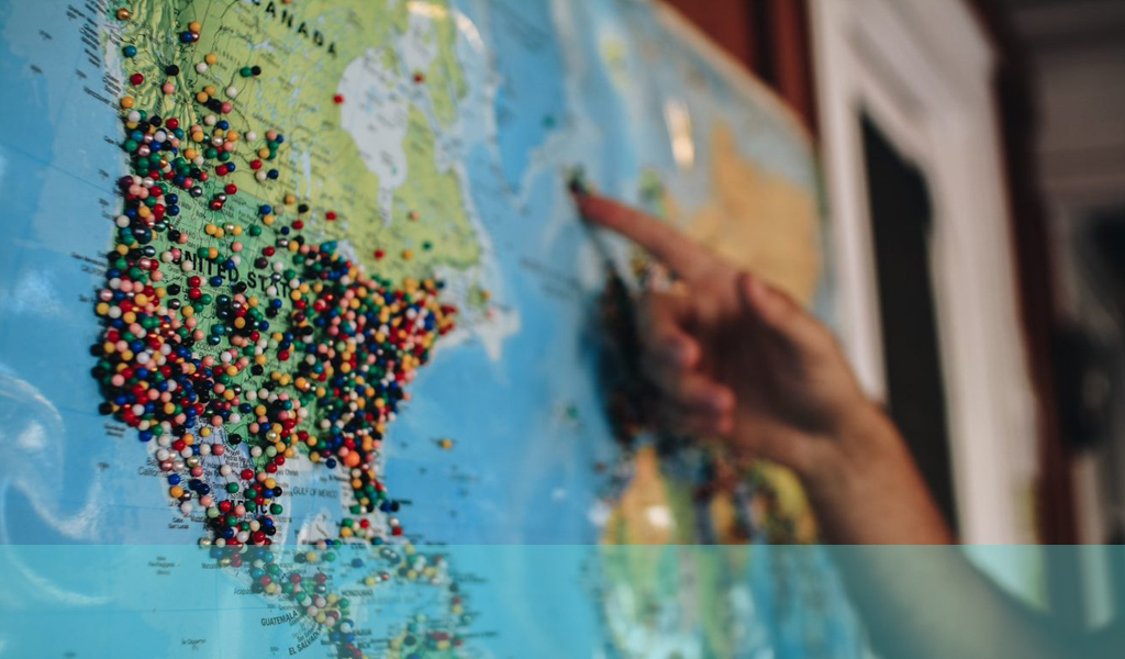 world map with pins in North and South America and a hand with finger pointing at Europe