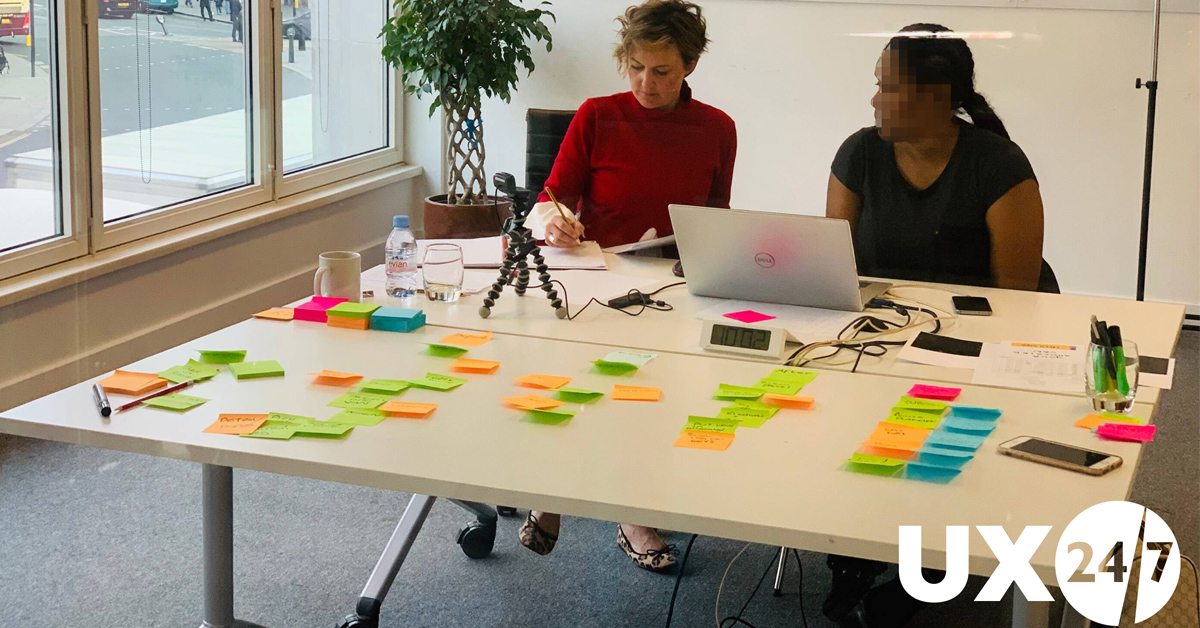 Photo of moderator working with participants in front of a table with post it nmotes spread out