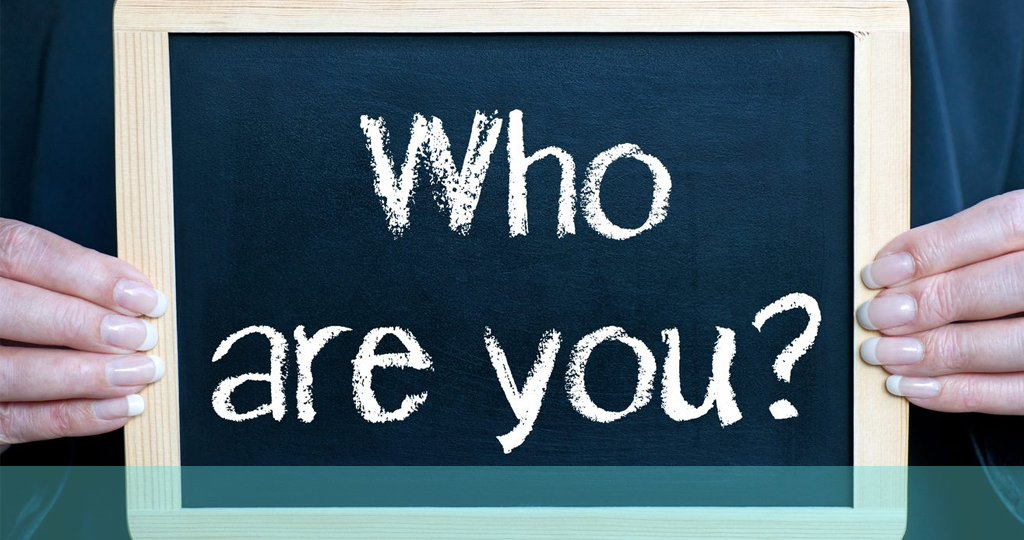 person holding chalk board that says who are you