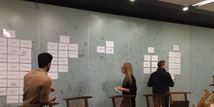 photo of stakeholders using a large board and post it notes